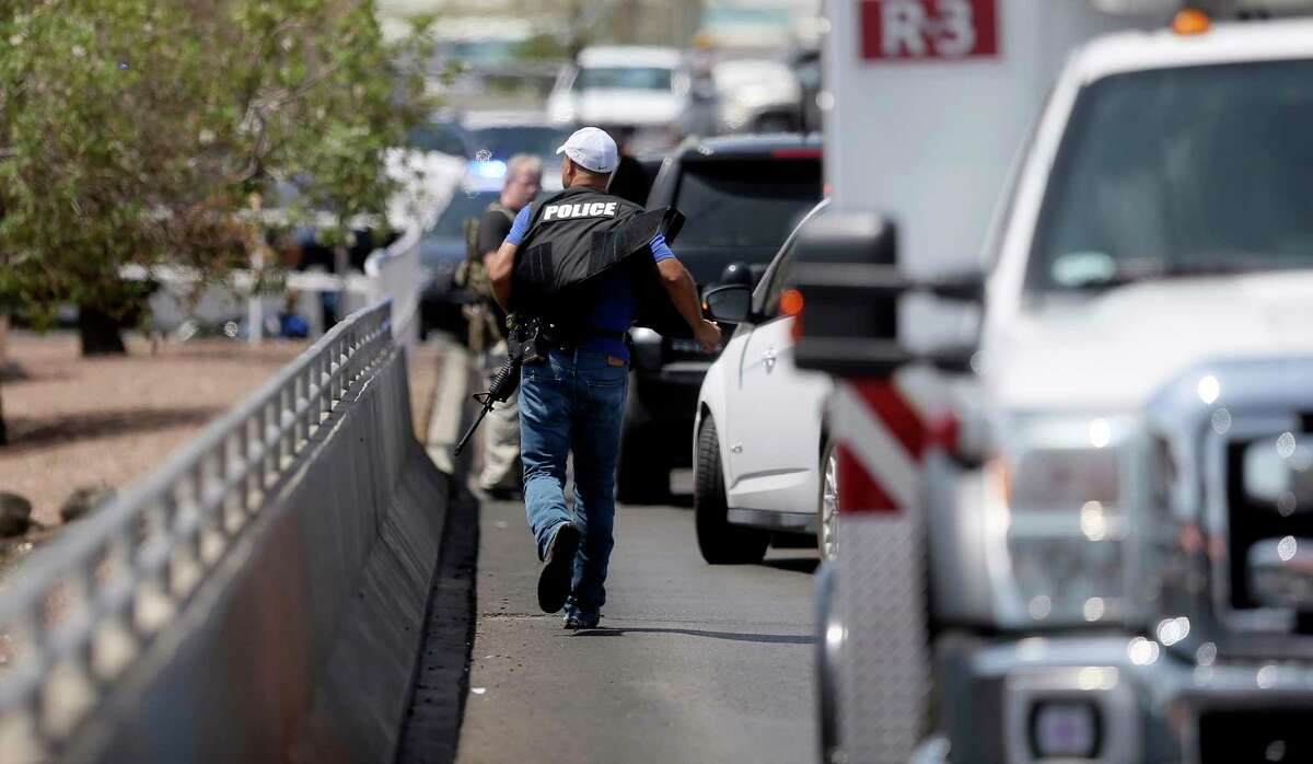 A police officer runs toward the scene of a shooting at a Walmart near Cielo Vista Mall in El Paso, Texas, Saturday, Aug. 3, 2019.