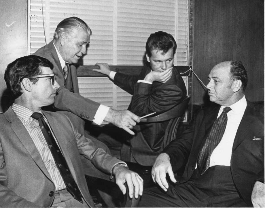Aug. 12, 1970: Charles V. Harrelson, pictured here third from the right moments after pleading not guilty in the murder of Houston carpet executive Alan Harry Berg, confers with Percy Foreman and other attorneys. Harrelson was eventually found not guilty in Berg's death – only to move on and assassinate U.S. District Judge John H. Wood in San Antonio.Charles Harrelson is the father of actor Woody Harrelson.  Photo: Darrell Davidson, Houston Chronicle / Houston Chronicle