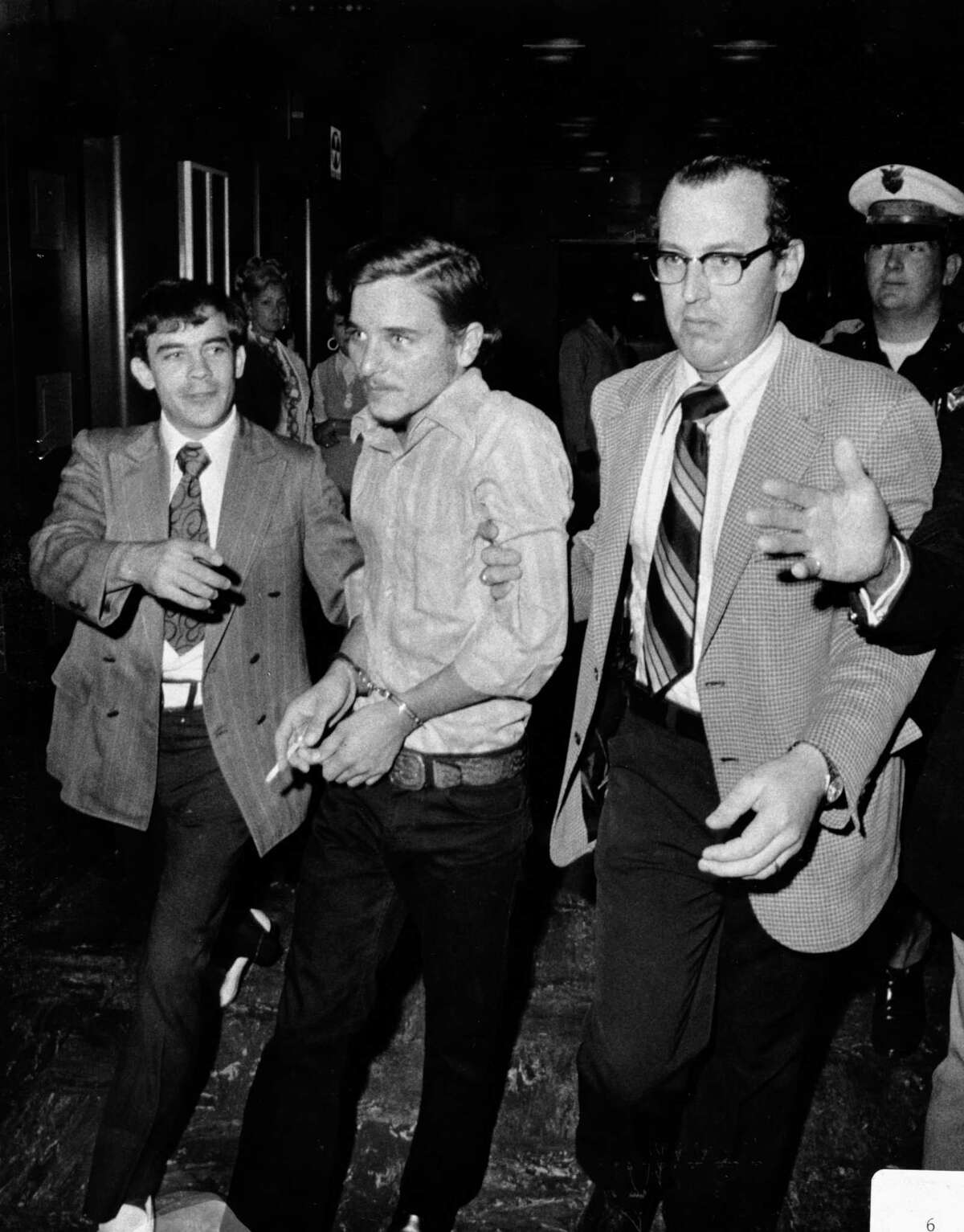 Aug. 13, 1973: A handcuffed Elmer Wayne Henley is escorted by police officers into a courtroom to face murder charges after he killed Dean Arnold Corll. Corll, who was known as The Candy Man, was a serial killer believed to have killed 28 teenage Houston boys, most of whom were lured by then-17-year-old Henley and a third teenage accomplice, David Owen Brooks. The murders came to light when Henley shot Corll Aug. 8, 1973. Henley is currently serving a 594-year sentence in the Texas State Penitentiary in Huntsville.