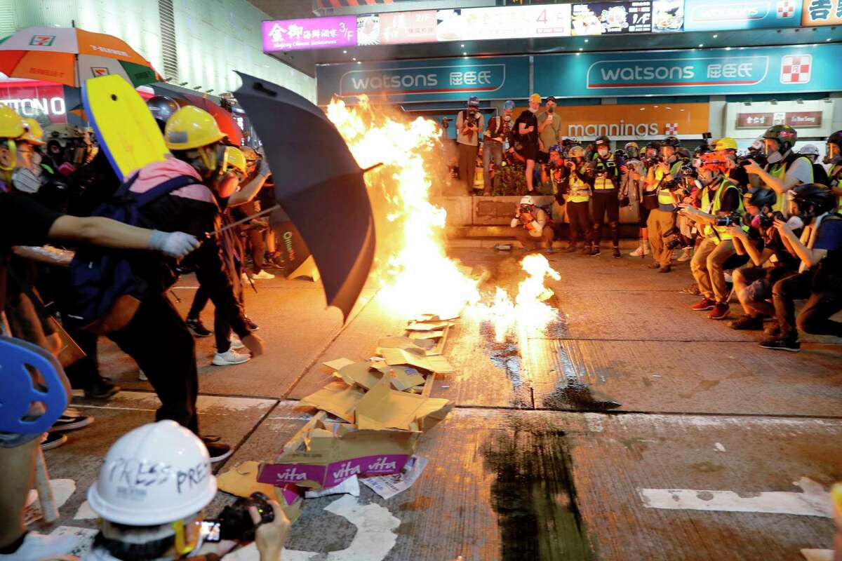 Protesters burn cardboard to form a barrier as they confront with police in Hong Kong on Saturday, Aug. 3, 2019. Hong Kong protesters removed a Chinese national flag from its pole and flung it into the city's iconic Victoria Harbour on Saturday, and police later fired tear gas at demonstrators after some of them vandalized a police station. (AP Photo/Kin Cheung)