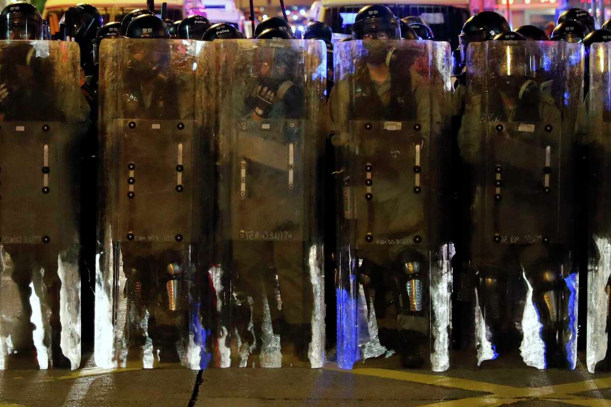 Riot police in protective gear form up during a confrontation with protesters in Hong Kong on Saturday, Aug. 3, 2019. Hong Kong protesters removed a Chinese national flag from its pole and flung it into the city's iconic Victoria Harbour on Saturday, and police later fired tear gas at demonstrators after some of them vandalized a police station. (AP Photo/Vincent Thian)