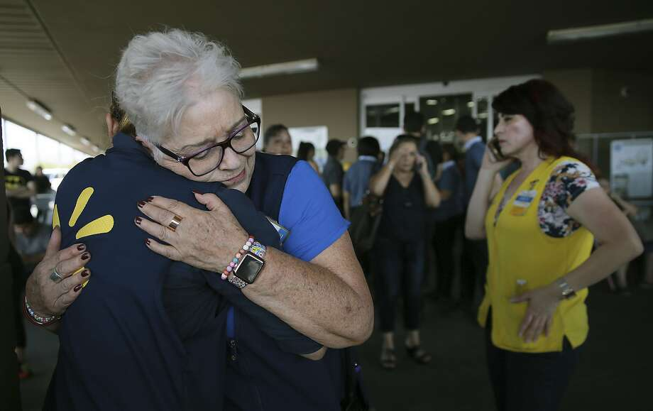 Walmart employees comfort one another after an active shooter opened fire at the store in El Paso, Texas, Saturday, Aug. 3, 2019. Photo: Mark Lambie, Associated Press