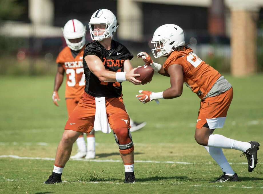 Texas quarterback Sam Ehlinger hands off to running back Keaontay Ingram at football practice at Whitaker Sports Complex on Friday. Photo: Jay Janner / Austin American-Statesman / Austin American-Statesman