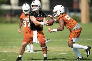 Texas quarterback Sam Ehlinger hands off to running back Keaontay Ingram at football practice at Whitaker Sports Complex on Friday.