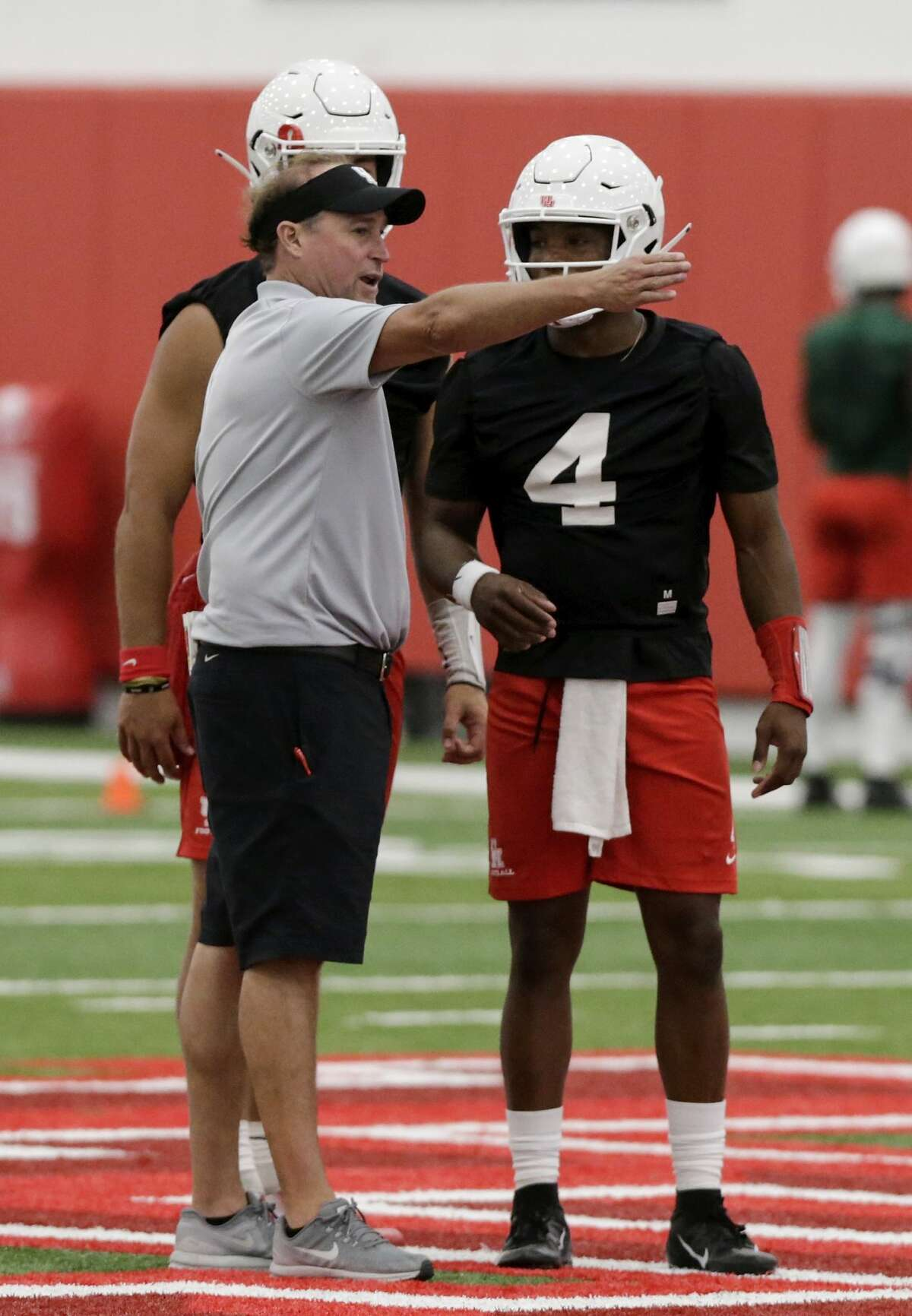 Houston Cougars head coach Dana Holgorsen talks with quarterback D'Eriq King (4) and quarterback Clayton Tune (3) during the first day of fall football practice at the University of Houston in Houston, TX on Saturday, August 3, 2019.