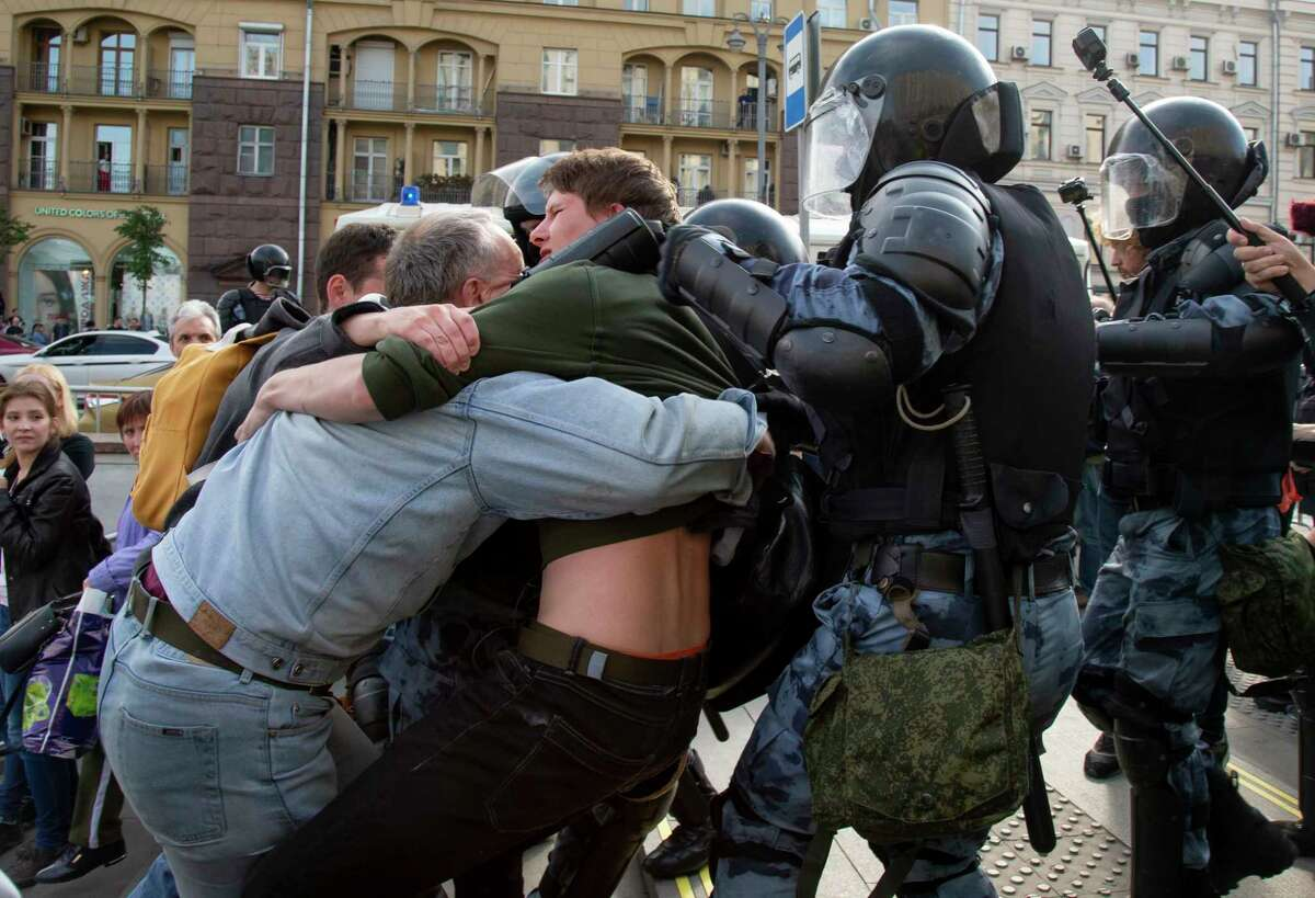 Police officers try to detain protestors during an unsanctioned rally in the center of Moscow, Russia, Saturday, Aug. 3, 2019. Moscow police detained more than 300 people Saturday who are protesting the exclusion of some independent and opposition candidates from the city council ballot, a monitoring group said. (AP Photo/Alexander Zemlianichenko)