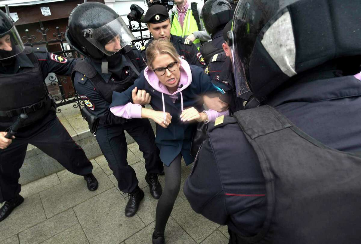 Police officers detain an opposition candidate and lawyer at the Foundation for Fighting Corruption Lyubov Sobol in the center of Moscow, Russia, Saturday, Aug. 3, 2019. Moscow police detained more than 300 people Saturday who are protesting the exclusion of some independent and opposition candidates from the city council ballot, a monitoring group said.(AP Photo/Dmitry Serebryakov)
