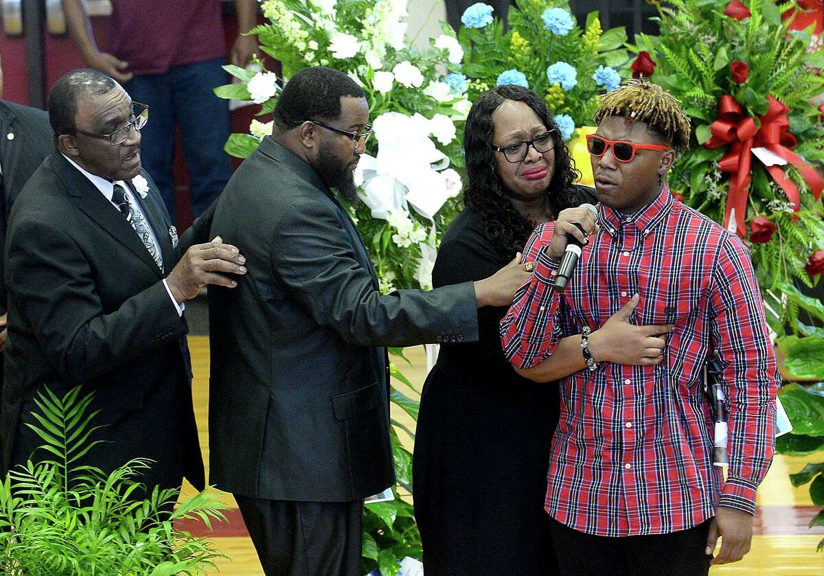 An older brother is supported by family as he speaks about his loss during Nicholas Trevon McBride's funeral services Saturday at Jasper Junior High School. The 12-year-old was accidentally shot and killed last weekend. Photo taken Saturday, August 3, 2019 Kim Brent/The Enterprise