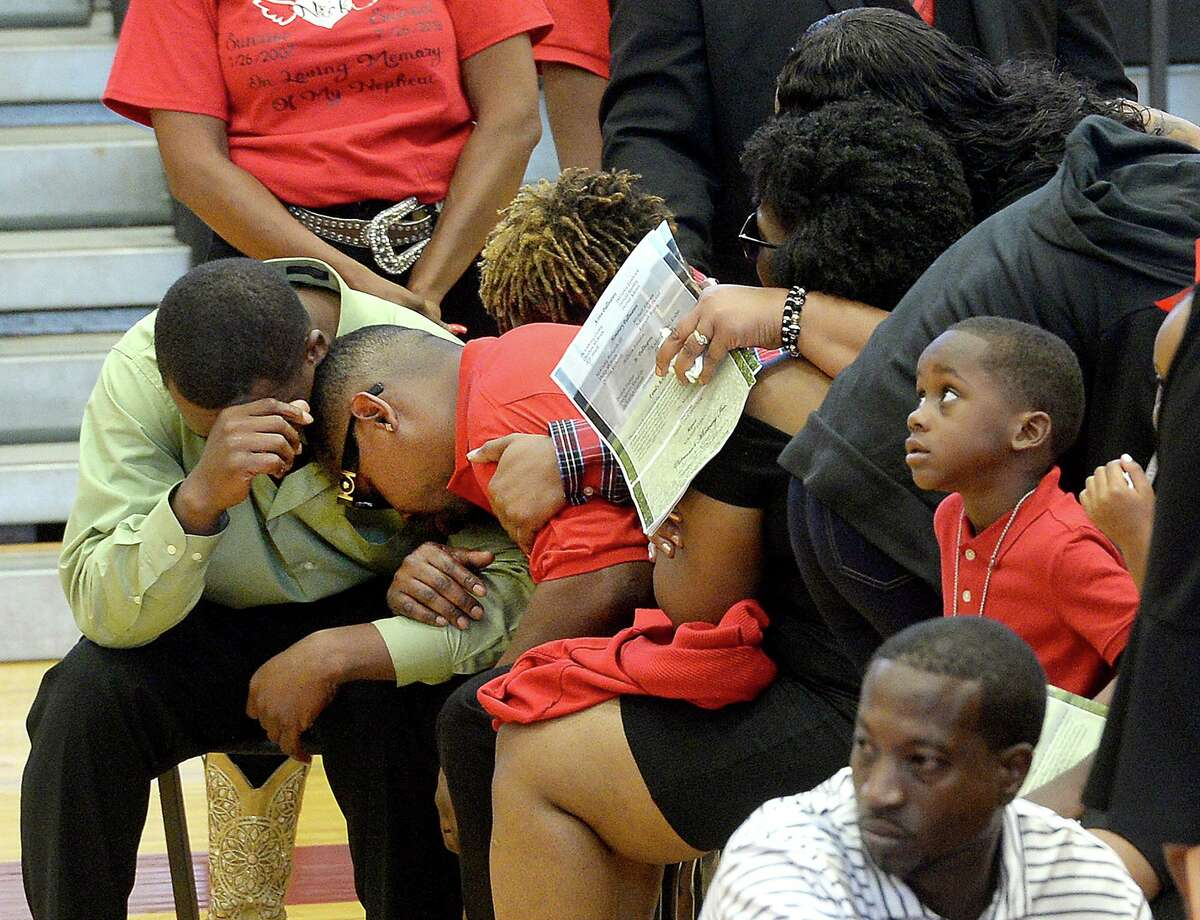 Father Jimmie McBride, Jr., is comforted by family after paying his final respects as members of the community and family gather in the gymnasium at Jasper Junior High School for Nicholas Trevon McBride's funeral services Saturday. The 12-year-old was accidentally shot and killed last weekend. Photo taken Saturday, August 3, 2019 Kim Brent/The Enterprise