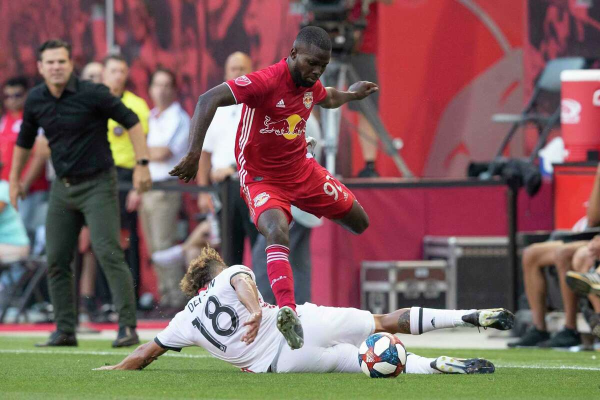 New York Red Bulls defender Kemar Lawrence (92) jumps over Toronto FC midfielder Nick DeLeon (18) while fighting for the ball during the first half of an MLS soccer match, Saturday, Aug. 3, 2019, in Harrison, N.J. (AP Photo/Mary Altaffer)