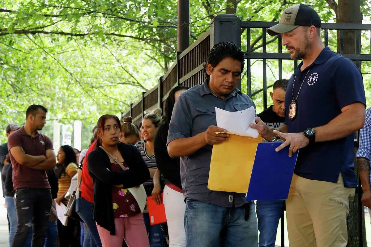 In this June 12, 2019, photo, an Immigration and Customs Enforcement official gives direction to a person outside the building that houses ICE and the immigration court in Atlanta. Immigration attorneys say the new timetable is too fast to prepare cases. The government has a goal of completing 56,000 cases in 10 cities in a year. (AP Photo/Andrea Smith)