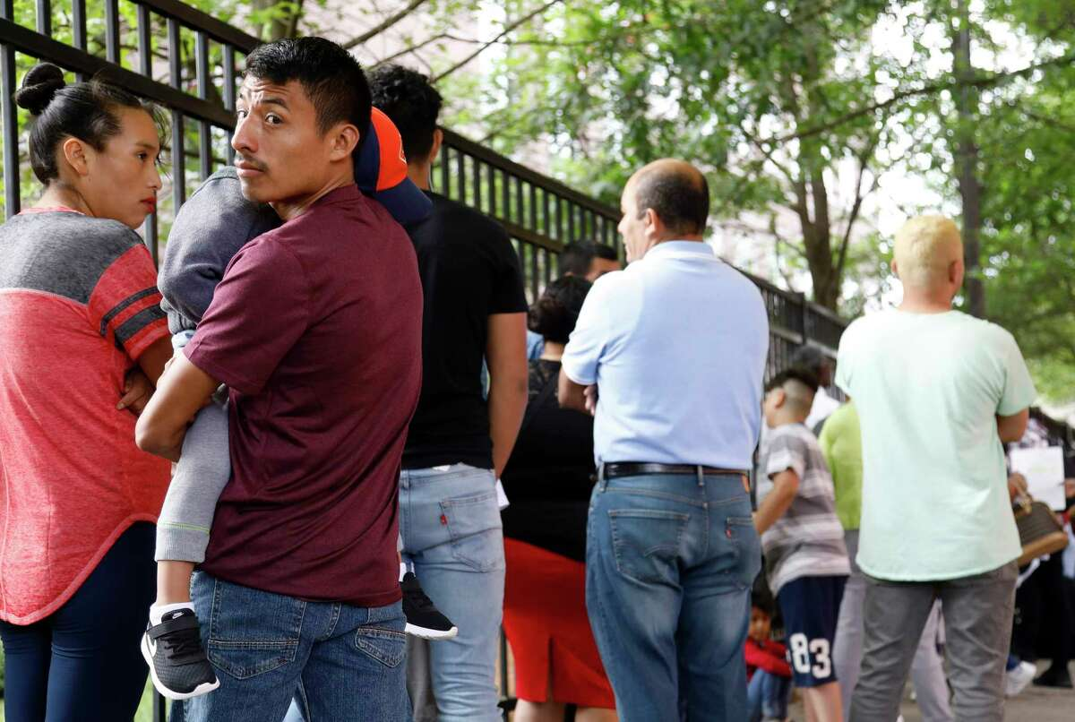 In this Wednesday, June 12, 2019 photo, Auner Cobon holds his son Andry while waiting in line outside the building that houses Immigration and Customs Enforcement and the Atlanta Immigration Court, in Atlanta. U.S. authorities are fast-tracking families' cases through immigration courts in a bid to discourage many from making the journey to seek refuge in the United States. (AP Photo/Andrea Smith)