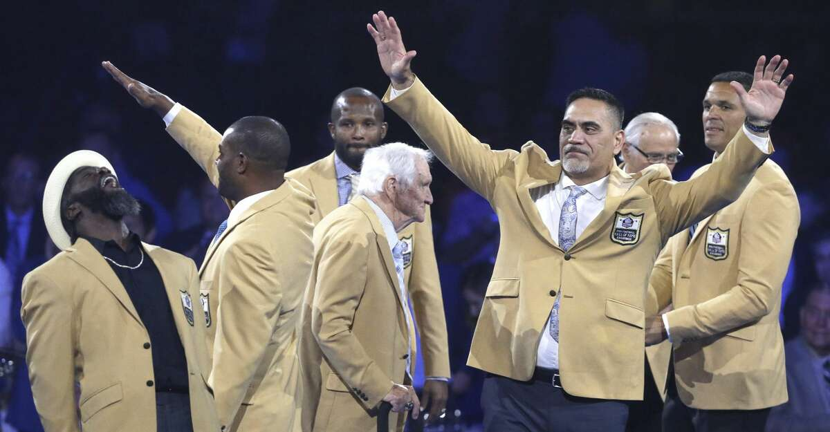 Member of the Pro Football Hall of Fame Class of 2019 react after receiving their gold jackets during the gold jacket dinner in Canton, Ohio, Friday, Aug. 2, 2019. From left are Ed Reed, Ty Law, Champ Bailey, Gil Brandt, Kevin Mawae, Johnny Robinson and Tony Gonzalez. (Scott Heckel/The Canton Repository via AP)