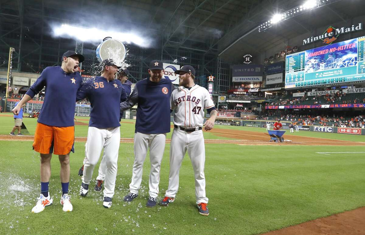 Houston Astros pitcher Collin McHugh sneaks up with a bucket of ice water to dump on starting pitcher Aaron Sanchez, left, and relief pitchers Will Harris (36), Joe Biagini (29) and Chris Devenski (47) pose after an MLB game at Minute Maid Park, Sunday, August 3, 2019. The Astros pitchers combined for a four-pitcher, no-hitter against the Seattle Mariners, and won the game 9-0.