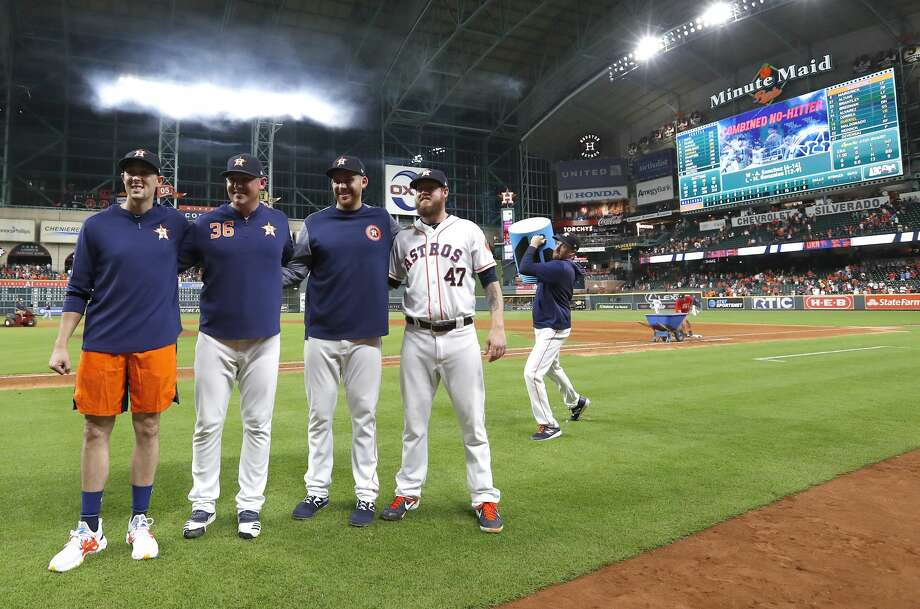 Houston Astros pitcher Collin McHugh sneaks up with a bucket of ice water to dump on starting pitcher Aaron Sanchez, left, and relief pitchers Will Harris (36), Joe Biagini (29) and Chris Devenski (47) pose after an MLB game at Minute Maid Park, Sunday, August 3, 2019.  The Astros pitchers combined for a four-pitcher, no-hitter against the Seattle Mariners, and won the game 9-0. Photo: Karen Warren/Staff Photographer