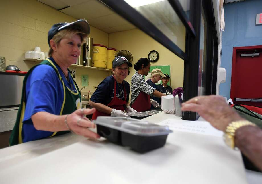 Donna Forgas, left, helps package food for Meals on Wheels at Some Other Place Monday.