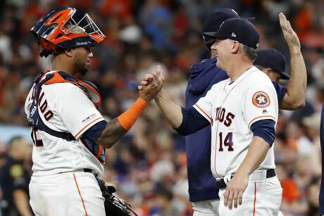 Houston Astros catcher Martin Maldonado (12) high fives manager AJ Hinch (14) as they celebrate the Astros combined no-hitter against the Seattle Mariners at Minute Maid Park on Saturday, Aug. 3, 2019, in Houston. Astros pitchers Aaron Sanchez, Will Harris, Joe Biagini and Chris Devenski completed the feat.
