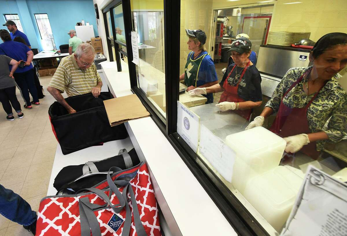 Meals on Wheels volunteers load containers with food at Some Other Place on Monday. Photo taken Monday, 7/29/19