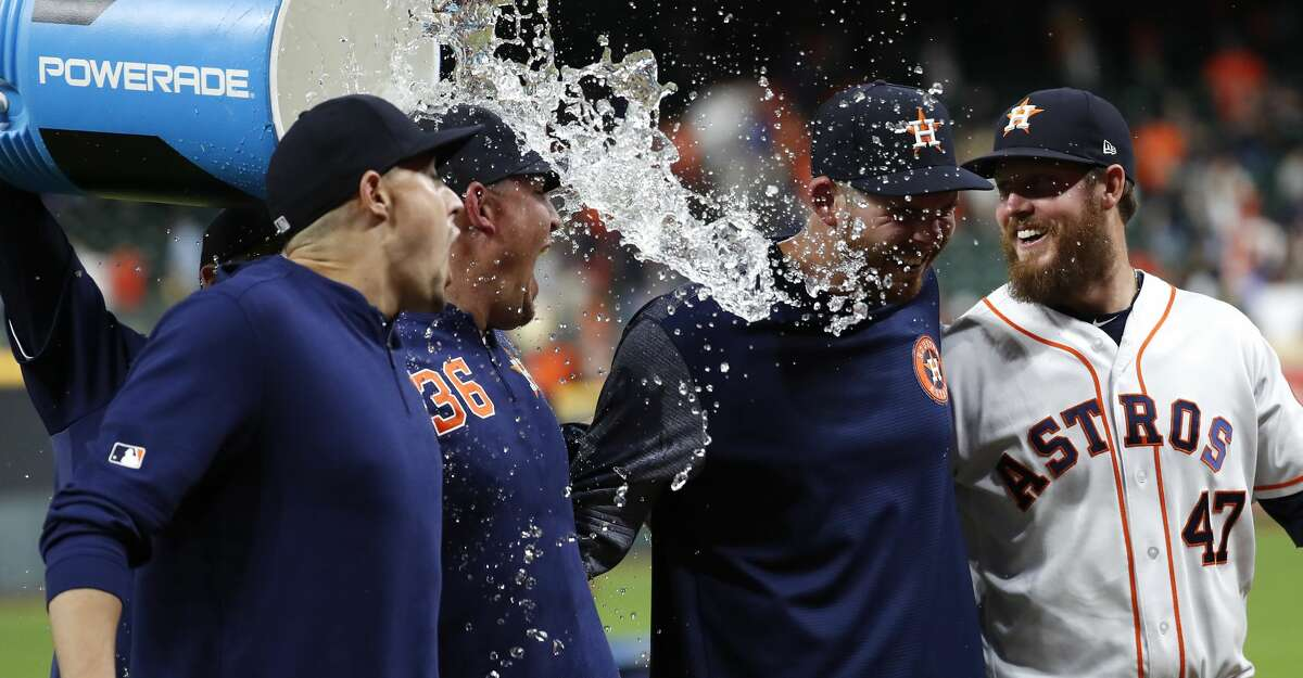 Houston Astros pitchers, from left, Aaron Sanchez, Will Harris (36), Joe Biagini and Chris Devenski (47) get doused with a bucket of water as they celebrate a combined no-hitter against the Seattle Mariners at Minute Maid Park on Saturday, Aug. 3, 2019, in Houston.