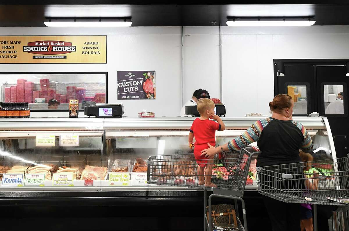 Joseph Hooper stands in a shopping cart while Brandi Hooper looks through meats at Mauriceville's newly opened Market Basket on Wednesday. Photo taken Wednesday, 7/31/19