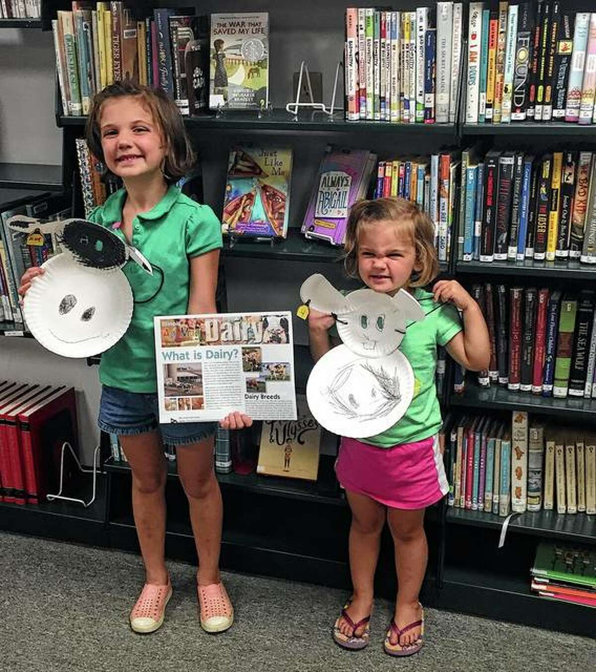 """Sisters Clara and Eleanore Nation show off their completed """"moo masks,"""" soybean crayons and beef/dairy agricultural magazines during a recent visit to Barry Public Library. The sisters, along with Jack Nation, explored agricultural education during a program led by Pike-Scott Farm Bureau's Agriculture in the Classroom program on behalf of the Two Rivers Farm Bureau Foundation. Along with making the mask and receiving a package of crayons made from soy, participants joined in as several ag-themed books were read during story time. The program, part of the library's summer reading program, runs from 5 to 6 p.m. Mondays until November."""