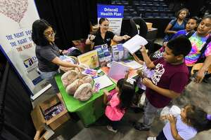 Garcia Early College Volunteer Danna Moreno helps Driscoll Health Plan's Jessica Martinez distribute scissors and reams of paper to students during the sixth annual Back 2 School Health Fair on Saturday at Sames Auto Arena.