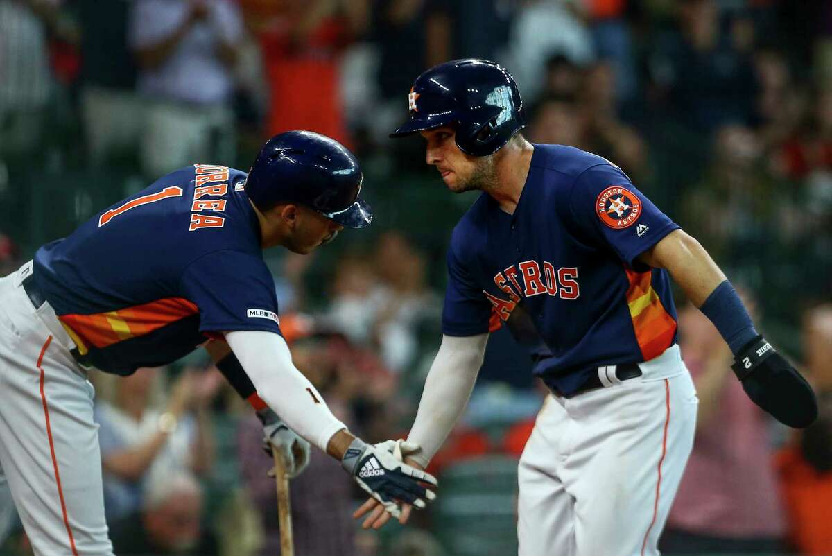 Houston Astros third baseman Alex Bregman (2) celebrates with shortstop Carlos Correa (1) while scoring off of left fielder Yordan Alvarez's (44) sacrifice fly during the sixth inning of an MLB game against the Seattle Mariners at Minute Maid Park Sunday, Aug. 4, 2019, in Houston.