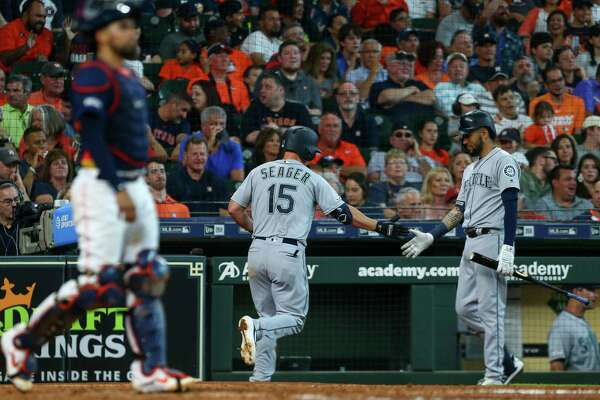 Seattle Mariners third baseman Kyle Seager (15) celebrates with shortstop J.P. Crawford (3) after hitting a home run against the Houston Astros during the seventh inning of an MLB game at Minute Maid Park Sunday, Aug. 4, 2019, in Houston.