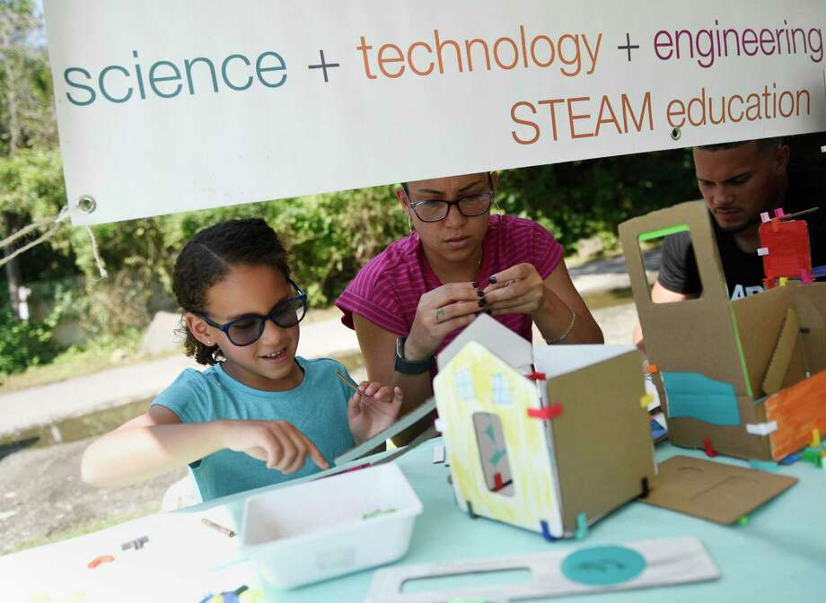 Stamford's Camila Pena, 6, creates an architectural model at the 3DuxDesign booth with her parents, Kelly and Henry, at the Art in the Garden for Kids event at Fort Stamford Park's Goodbody Garden in Stamford, Conn. Sunday, Aug. 4, 2019. Presented by the Stamford Garden Club, the event featured music from local artist Brittany Santacroce as well as many children's activities including drawing, crafts, robotics, writing and more. Photo: Tyler Sizemore / Hearst Connecticut Media / Greenwich Time