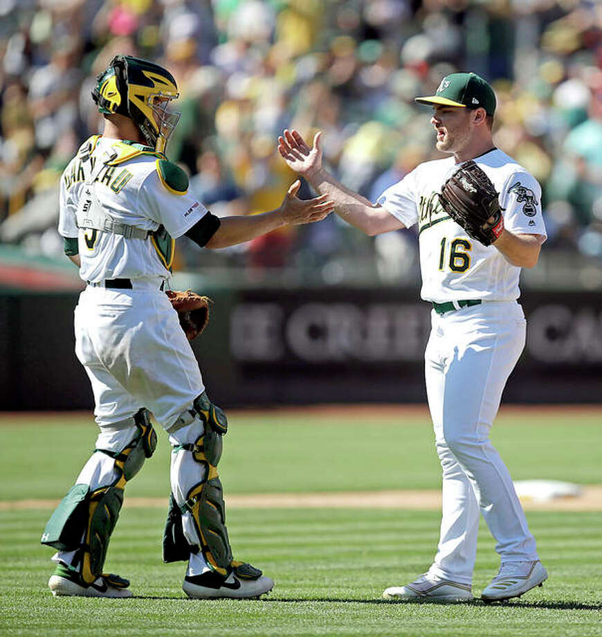 Oakland Athletics pitcher Liam Hendriks, right, and Dustin Garneau celebrate their team's 4-2 win over the Cardinals Sunday in Oakland, Calif. Photo: AP Photo