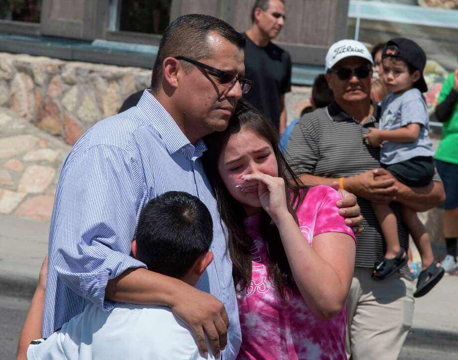 "Members of the Medina family react beside a makeshift memorial outside the Cielo Vista Mall Wal-Mart (background) where a shooting left 20 people dead in El Paso, Texas, on August 4, 2019. - Texas authorities are investigating the Saturday mass shooting at a Walmart store in El Paso as a possible hate crime, the city's police chief said, as authorities study an online manifesto linked to the suspect. A 21-year-old from Allen, a suburb of Dallas, surrendered to police outside the store after the rampage that left 20 people dead and 26 wounded.US media identified him as Patrick Crusius, who is white, and linked him to a ""manifesto"" posted online that includes passages railing against the ""Hispanic invasion"" of Texas. (Photo by Mark RALSTON / AFP)MARK RALSTON/AFP/Getty Images Photo: MARK RALSTON, Contributor / AFP/Getty Images / AFP or licensors"