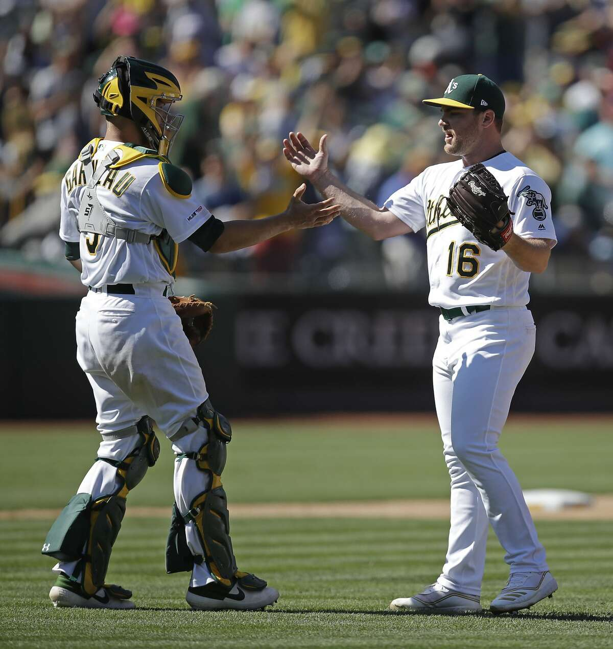 Oakland Athletics pitcher Liam Hendriks, right, and Dustin Garneau celebrate the 4-2 win over the St. Louis Cardinals at the end of a baseball game Sunday, Aug. 4, 2019, in Oakland, Calif. (AP Photo/Ben Margot)