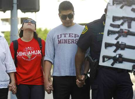 Stephanie Reveles and Adrian Lira, both originally from El Paso, participate in a gathering to honor the victims of the recent mass shootings in El Paso, TX and Dayton, OH, in downtown Houston, Sunday, Aug. 4, 2019.