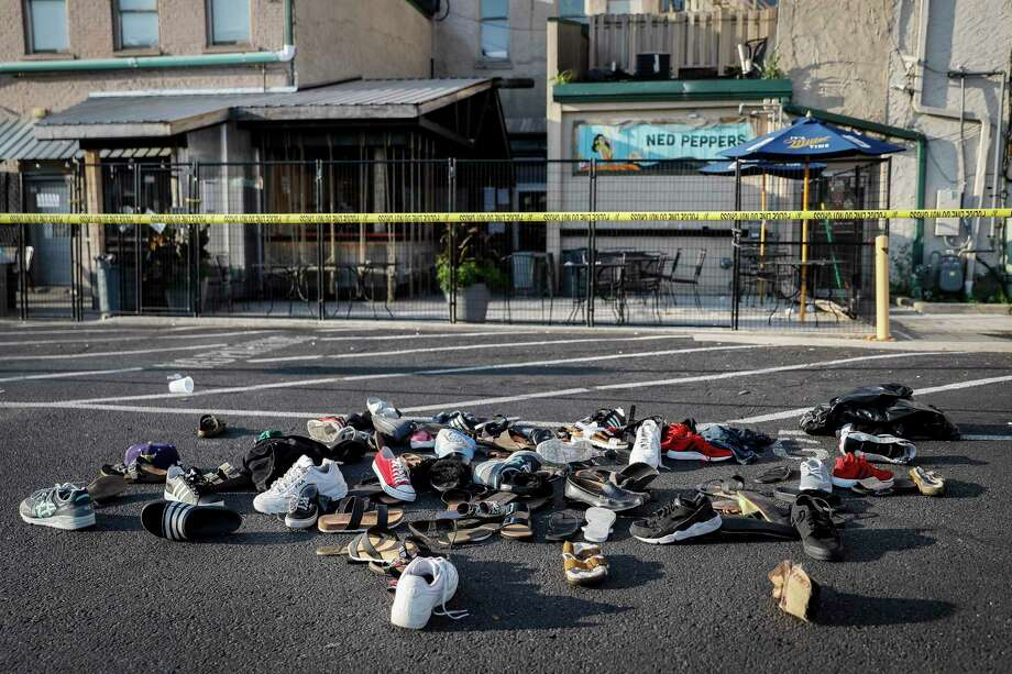 Shoes are piled outside the scene of a mass shooting including Ned Peppers bar, Sunday, Aug. 4, 2019, in Dayton, Ohio. Several people in Ohio have been killed in the second mass shooting in the U.S. in less than 24 hours, and the suspected shooter is also deceased, police said. (AP Photo/John Minchillo) Photo: John Minchillo / Copyright 2019 The Associated Press. All rights reserved.
