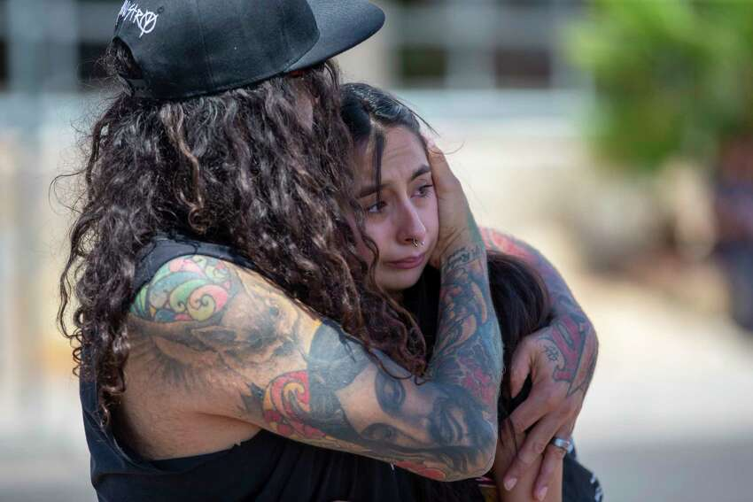A couple embrace at the makeshift memorial for the victims of Saturday mass shooting at a shopping complex in El Paso, Texas, Sunday, Aug. 4, 2019. (AP Photo/Andres Leighton)