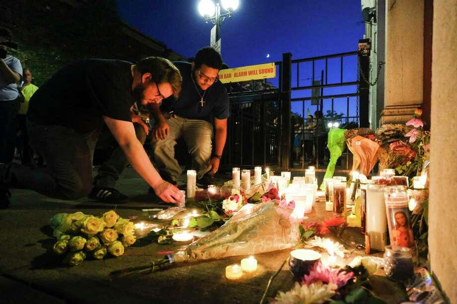 Residentes encienden velas en la entrada de Ned Peppers Bar en una vigilia en Dayton, Ohio, donde tuvo lugar un tiroteo masivo durante las primeras horas del domingo, 4 de agosto de 2019. Al menos nueve personas murieron y otras 27 resultaron heridas, según autoridades. Fue el segundo tiroteo masivo mortal en menos de 24 horas, y el tercero en una semana. Photo: AJ Mast /NYT / NYTNS