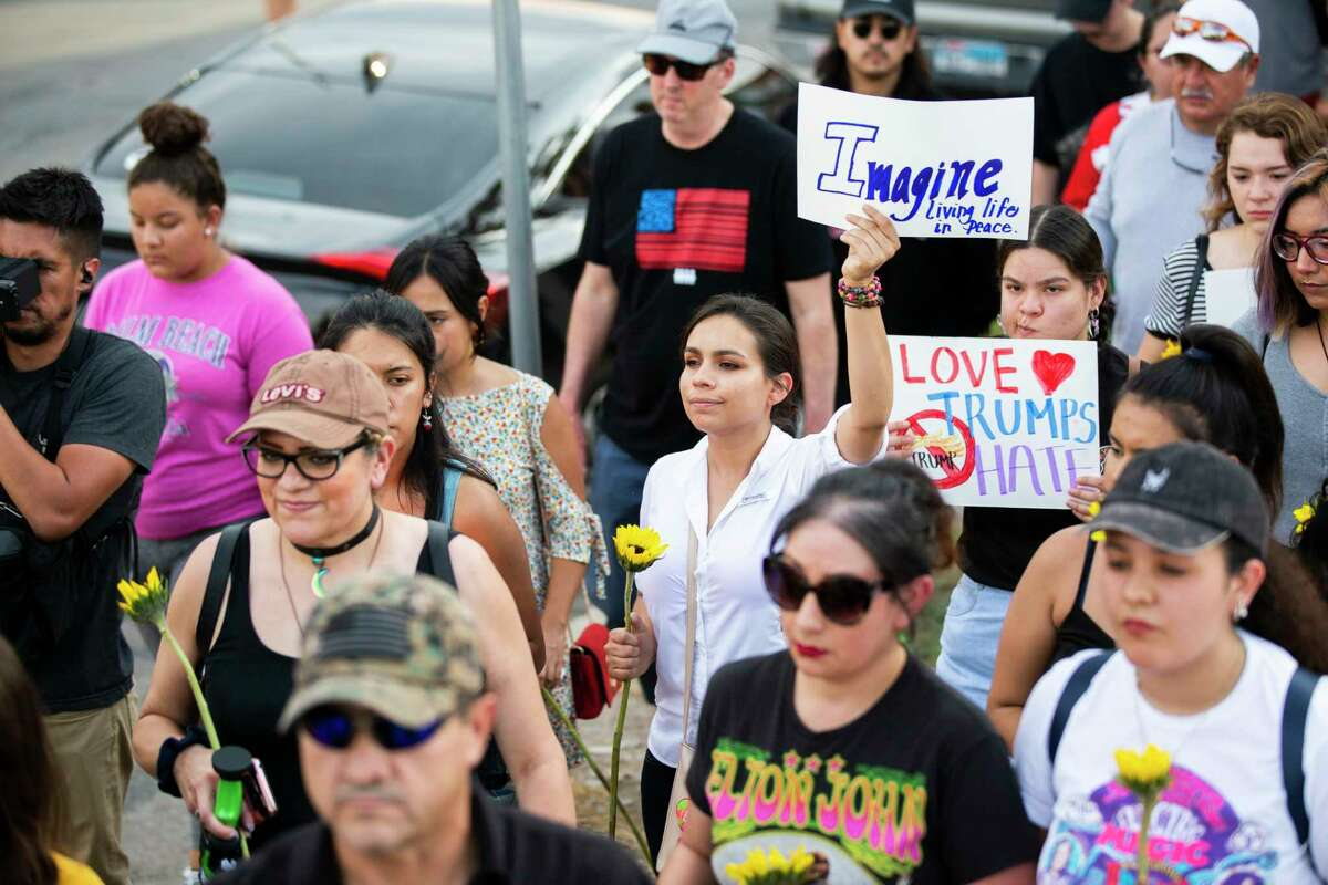 Protestors demonstrate in silence against violence during a procession holding signs on their way to Las Americas Headquarters Sunday, Aug. 4, 2019, in El Paso.