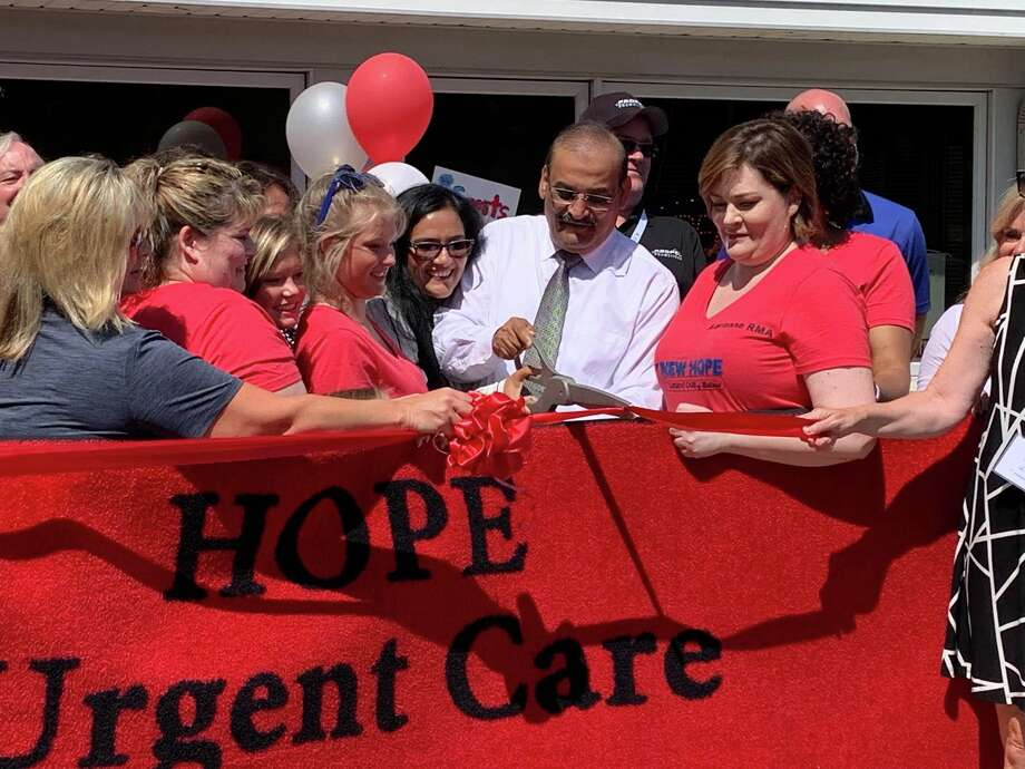 Zaher Sherwani, surrounded by employees and office staff of New Hope Urgent Care, cuts a ribbon to commemorate the one-year anniversary of the organization's West Wackerly Street location on Aug. 2, 2019. (Mitchell Kukulka/Mithcell.Kukulka@mdn.net). Photo: Mitchell Kukulka