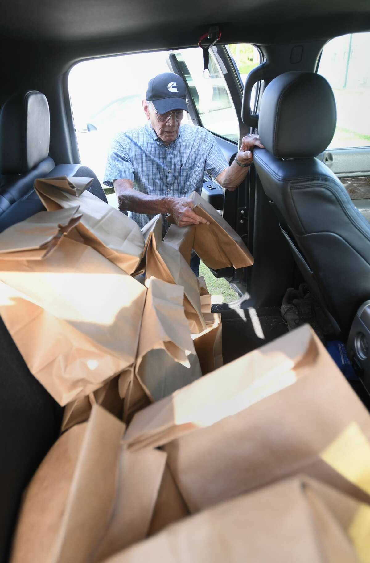 Meals on Wheels volunteers Daryl Ferguson loads his truck with bags of food before driving his route. Ferguson and his partner deliver food to 31 homes on his route. Photo taken Monday, 7/29/19
