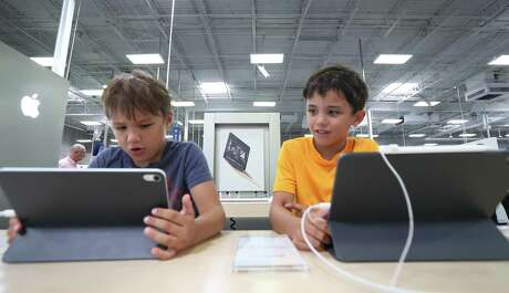 Clive Pilson, 7, (left) and his brother Rohan, 9, look at iPads at Best Buy Wednesday, July 31, 2019, in Houston.