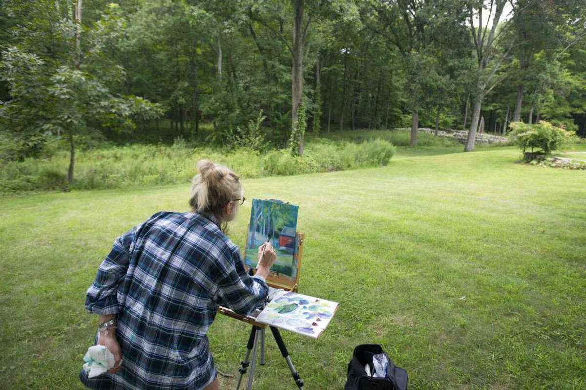 Artist Andrea McLaughlin, of Wilton, paints an outdoor scene in acrylics during the 2018 Art in the Park Festival.