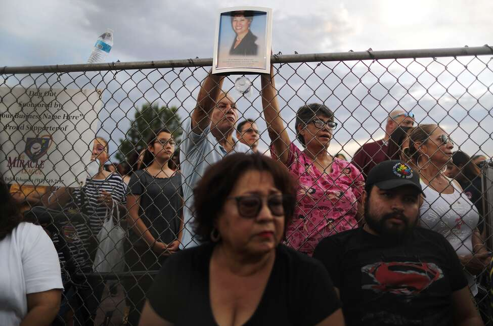 A photo (top) of Elsa Mendoza Marquez, a Mexican schoolteacher from Ciudad Juarez who was killed in the shooting, is held up during an interfaith vigil for victims of a mass shooting, which left at least 20 people dead, on August 4, 2019 in El Paso, Texas.