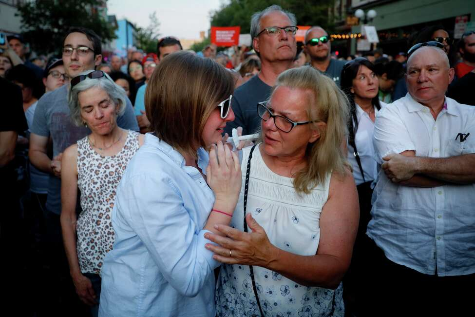 Mourners comfort one another during vigil at the scene of a mass shooting, Sunday, Aug. 4, 2019, in Dayton, Ohio. Multiple people in Ohio have been killed in the second mass shooting in the U.S.