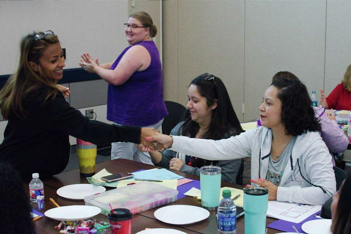 Pre-K teachers Maria Izaguime, left, Susi McDaniel, Denisse Saldivar and Maria Arriaga participate in a workshop activity where they learn how germs are spread through human contact.