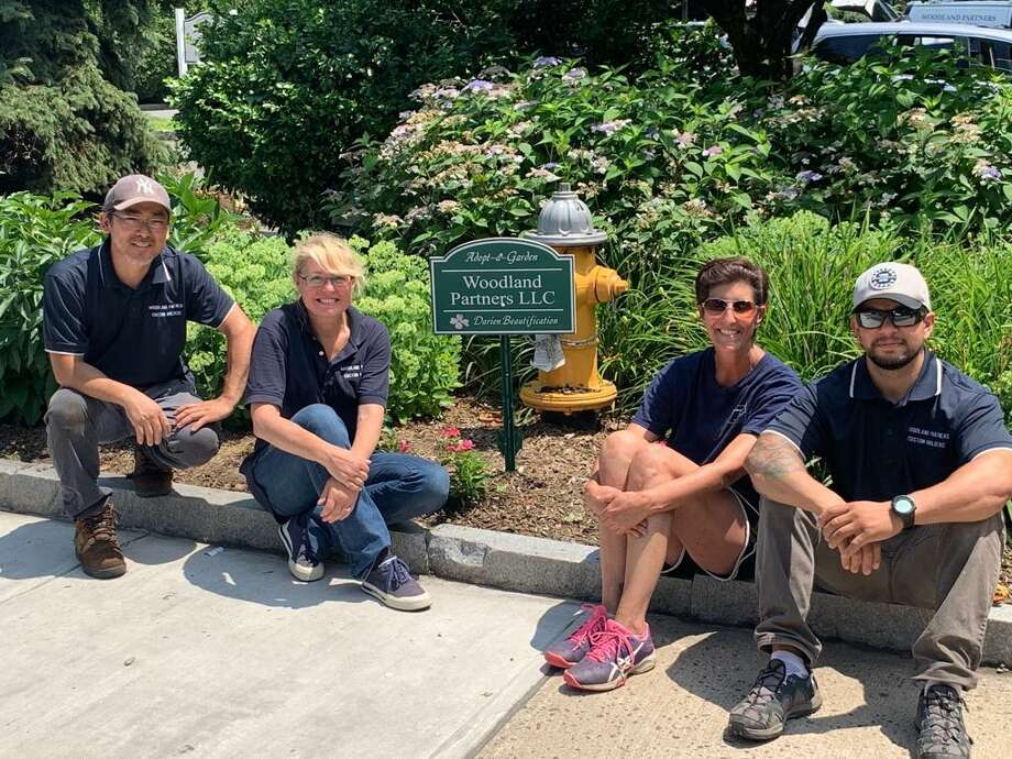 Leo Leles, Amber Penberty, Kristen Luckente and Germano Ikaro of Woodland Partners recently participated in the town's Adopt-a-Garden program. Photo: Contributed /