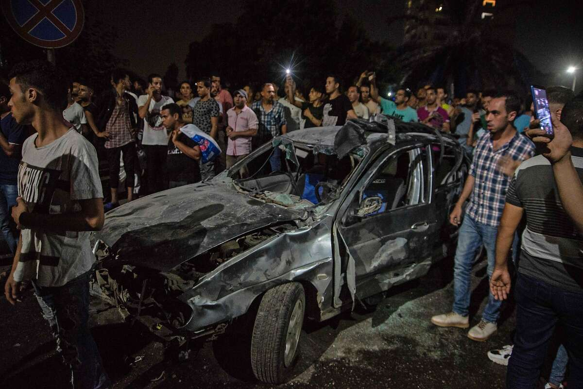 Onlookers gather around a charred car, following an accident just before midnight on August 4, 2019, outside the National Cancer Institute in the Egyptian capital Cairo. - At least 19 people have been killed and more than 30 injured when a speeding car driving against traffic crashed into three others causing a huge explosion in the capital, the Egyptian health ministry said today. (Photo by Aly FAHIM / AFP)ALY FAHIM/AFP/Getty Images