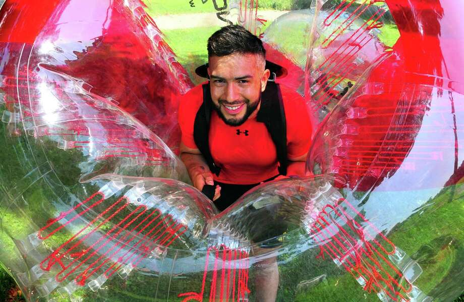 J. David Ospina poses as he holds a weekly gathering to enjoy games using bubble balls at Scalzi Park in Stamford on Saturday. Ospina holds a weekly gathering to enjoy games using the bubble balls and as an incentive to do area beautification & clean-up in the park after the event. Photo: Christian Abraham / Hearst Connecticut Media / Connecticut Post