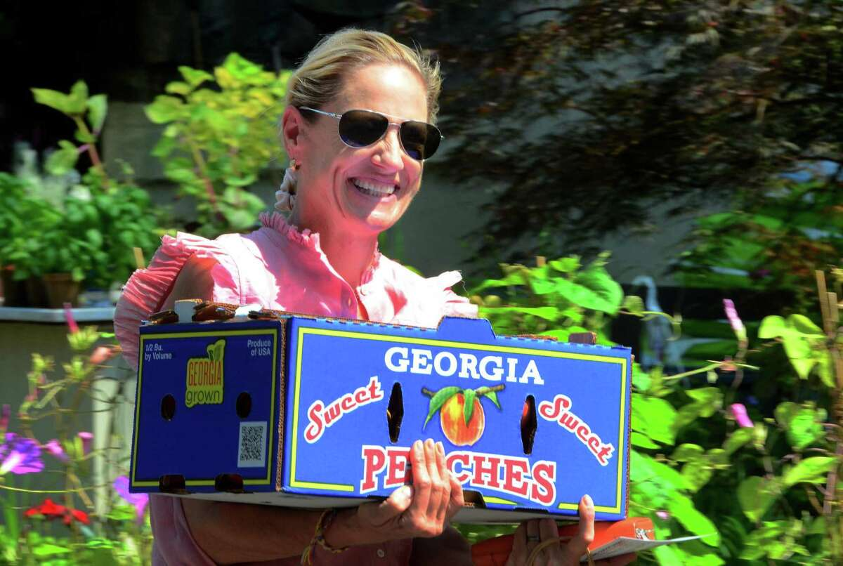 Customer Icy Fantz, of Greenwich, carries a box of peaches to her car as the Georgia Peach Truck visits McArdle's Florist & Garden Center as part of its East Coast Road Trip 2019 in Greenwich, Conn., on Saturday August 3, 2019. If you can't make it out to the truck this week, you can catch it later this month: July 30 Westport: 9 a.m. to 10:30 a.m. at Gilbertie's Garden Center Darien: 12 p.m. to 1:30 p.m. at The Gardener's Center and Florist Greenwich: 3 p.m. to 4:30 p.m. at McArdle's Florist and Garden Center