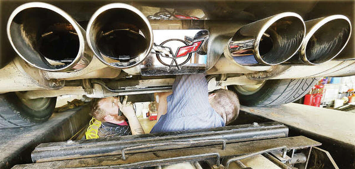 Employees of Meineke Car Care Center in Wood River on Monday work to catch and remove a part-Siamese kitten from the rear undercarriage of a Chevrolet Corvette belonging to retired Roxana High School football coach Bill Smith after the cat climbed up under his car in the Wood River McDonald's parking lot and would not come out. A woman originally called Wood River animal control because the cat was hiding in the wheel of her Honda Pilot; it then fled to the nearby Corvette, touching off an hour-long ordeal to get the kitten out.