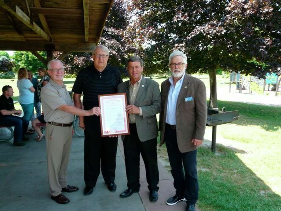From left, Williams TownshipSupervisor Paul Wasek, Bay County Commissioner Vaughn Begick, State Rep. Kevin Daley and Bay County Board of Commissioners Chair Michael Duranczyk display a State of Michigan Proclamation as part of a Williams Township Park Dedication in memory of Connie Hoverman. The longtime township treasurer was honored for her instrumental role in the building of a new children's play area in Williams Township Park. (Photo provided/Jon Becker)
